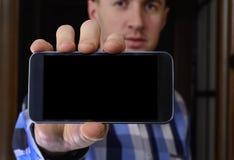 Молодой человек в checkered голубой рубашке держит телефон с стоковое изображение rf