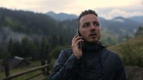 Молодой человек говорит на телефоне в вечере в горах Вокруг леса в тумане сток-видео