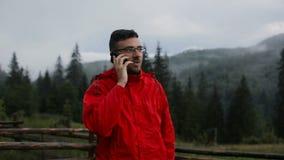 Молодой человек говорит на телефоне в вечере в горах Вокруг леса в тумане акции видеоматериалы
