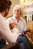 Молодой человек говоря к консультанту используя таблетку цифров Стоковые Фото