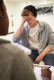 Молодой человек говоря к консультанту который принимает примечания стоковая фотография rf
