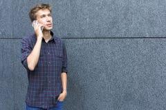 Молодой человек говоря на космосе экземпляра телефона внешнем стоковая фотография