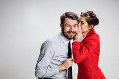Молодой человек говоря сплетни к его коллеге женщины на офисе Стоковые Изображения