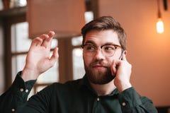 Молодой человек говоря телефоном и развевая взглядом в сторону Стоковая Фотография