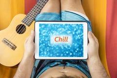 Молодой человек лежа на гамаке при прибор таблетки смотря запачканную голубую предпосылку с словом & x22; Chill& x22; написанный  Стоковая Фотография