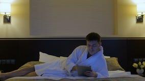 Молодой человек лежит на кровати в гостинице и смотрит в телефон, таблетку акции видеоматериалы