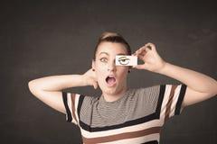 Молодой человек держа бумажным с сердитым чертежом глаза Стоковое Изображение RF