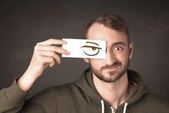 Молодой человек держа бумажным с сердитым чертежом глаза Стоковое Изображение