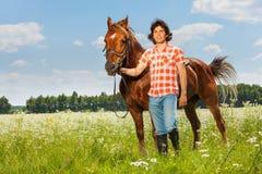 Молодой человек держа его коричневую лошадь уздечкой стоковые фото