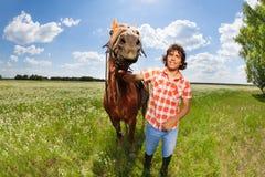 Молодой человек держа его красивую лошадь уздечкой стоковое фото