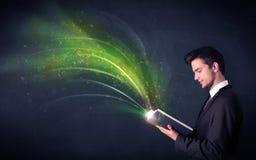 Молодой человек держа книгу с волной Стоковые Изображения RF