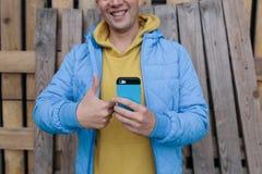 Молодой человек держа мобильный телефон в одной руке, и другой показ большие пальцы руки Стоковые Изображения
