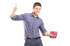 Молодой человек держа настоящий момент и давая большой палец руки вверх Стоковые Фото