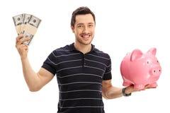 Молодой человек держа пачки денег и piggybank Стоковое Изображение RF