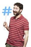 Молодой человек держа социальные средства массовой информации подписывает усмехаться стоковые изображения rf