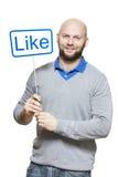 Молодой человек держа социальные средства массовой информации подписывает усмехаться стоковые фото