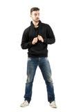 Молодой человек держа строки hoodie смотря вниз Стоковое Фото