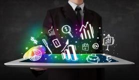 Молодой человек держа таблетку с символами диаграммы и диаграммы Стоковые Фото