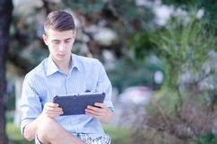 Молодой человек держа таблетку стоковые фото