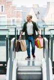 Молодой человек держа хозяйственные сумки пока стоящ на эскалаторе и смотрящ прочь стоковая фотография
