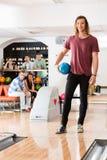 Молодой человек держа шарик на клубе боулинга Стоковые Изображения