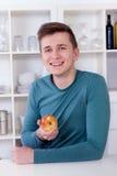 Молодой человек есть здоровое яблоко в его кухне Стоковая Фотография RF