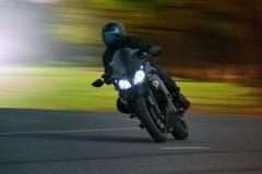 Молодой человек ехать большой мотоцикл велосипеда на пути асфальта высоком против стоковая фотография rf