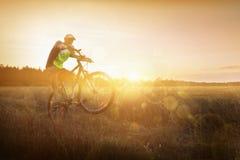 Молодой человек ехать велосипед на заходе солнца Стоковое фото RF