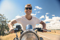 Молодой человек ехать его мотоцилк на открытой дороге Стоковая Фотография RF