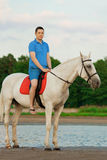 Молодой человек ехать лошадь на заходе солнца на пляже Человек с hors Стоковое Фото
