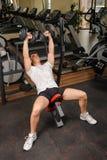 Молодой человек делая разминку жима лёжа уклона гантели в спортзале Стоковые Изображения RF
