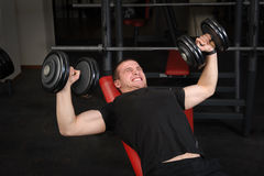 Молодой человек делая разминку жима лёжа уклона гантели в спортзале Стоковое фото RF