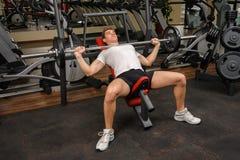 Молодой человек делая разминку жима лёжа уклона штанги в спортзале Стоковые Изображения RF