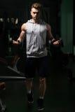 Молодой человек делая тренировку для бицепса с гантелями Стоковые Фото