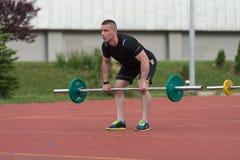 Молодой человек делая тренировку Deadlift внешнюю Стоковое фото RF