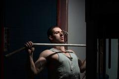Молодой человек делая тяжеловесную тренировку для задней части Стоковое Фото