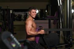 Молодой человек делая тяжеловесную тренировку для задней части Стоковое фото RF