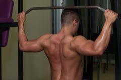 Молодой человек делая тяжеловесную тренировку для задней части Стоковое Изображение RF