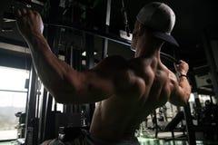 Молодой человек делая тяжеловесную тренировку для задней части Стоковые Фото