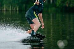 молодой человек едет wakeboard на озере стоковое фото rf