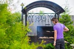 Молодой человек жарит стейки на гриле внешнем в его дворе стоковая фотография rf