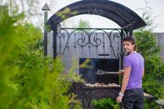 Молодой человек жарит стейки на гриле внешнем в его дворе Стоковое фото RF