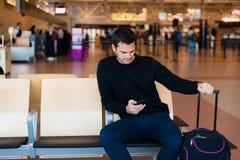 Молодой человек ждать в международном аэропорте Стоковые Фотографии RF