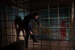 Молодой человек заключенный в турьму в клетке металла с кровью splattered wal Стоковая Фотография RF