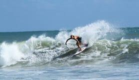 Молодой человек занимаясь серфингом в Kuta стоковое изображение rf