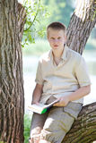Молодой человек (зрачок, студент) читает книгу на банке реки Стоковое Фото