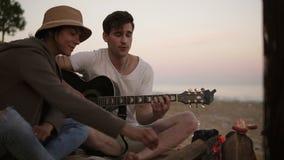 Молодой человек играет гитару огнем сидя на пляже вместе с друзьями Его подруга жаря сосиску акции видеоматериалы