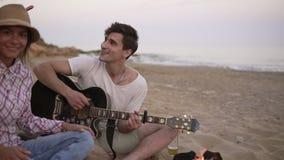 Молодой человек играет гитару огнем сидя на пляже вместе с друзьями Его подруга принося зажаренное акции видеоматериалы