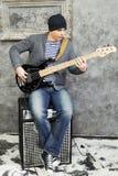 Молодой человек играет гитару сидя на усилителе стоковая фотография rf