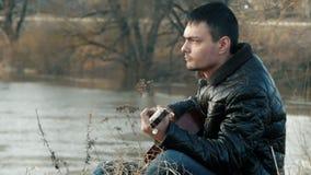 Молодой человек играя гитару около реки ретро акции видеоматериалы